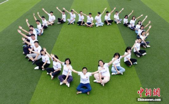 6月3日,湖南道县第一中学高三年级学生在校园里摆出各种姿势拍摄创意毕业照,定格青春美好回忆,以此调适心态迎接高考。何红福 摄