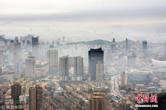 7月4日下午,山东烟台市芝罘区,海面出现平流雾。隔海望去,雾气笼罩中的山仿佛悬浮在空中一般。刘臣臣 摄 图片来源:视觉中国