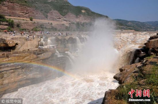 7月5日,山西临汾,游人在黄河壶口瀑布游览。近日,位于秦晋大峡谷的黄河壶口瀑布水量增大,彩虹镶嵌,气势磅礴。苏强 摄 图片来源:视觉中国