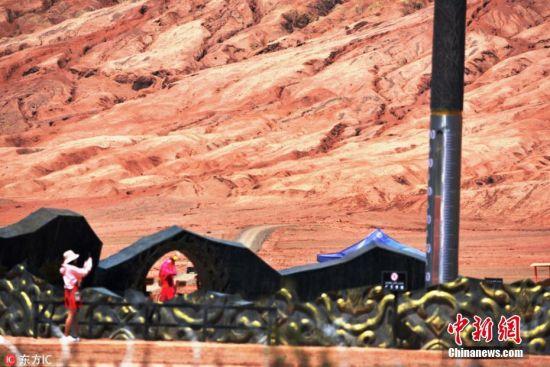 """7月10日,新疆吐鲁番火焰山风景区高温时段的实时地表温度接近80℃,市区最高温度持续达到40℃。据了解,进入7月份以来,有""""火洲""""之称的新疆吐鲁番盆地持续出现高温天气,局部地区最高温度达到45℃,距离市区40多公里的火焰山风景区最高温度超过了50℃,高温时段的实时地表温度达到85℃。持续高温天气拉动了当地的旅游业,众多游客纷纷前来体验火洲的""""非凡热度"""",仅火焰山风景区每天游客数量达到2000多人次;同时,持续高温天气还当地的葡萄和其他瓜果的成熟和品质带来了好处,葡萄的成熟期比往年提前了十天左右。姜晓明 摄 图片来源:东方IC 版权作品 请勿转载"""