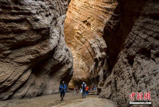 7月10日,游客在新疆库车的天山大峡谷中游览,领略大自然的鬼斧神工。天山库车大峡谷,又称克孜利亚大峡谷,位于阿克苏地区库车县北部,呈东向西纵深长约5.5公里。山体为红褐色岩石经风雕雨刻而成,峡谷曲径通幽,别有洞天。中新社记者 刘新 摄