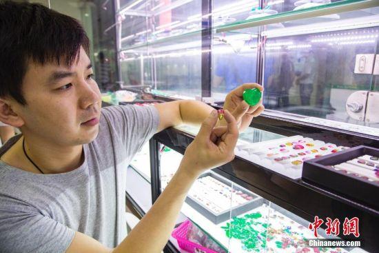 """7月24日,广西梧州一宝石商城内,珠宝商人简国雄展示自己工厂内加工合成的多种拼石,其产品主要以立方氧化锆、玻璃以及天然石的裸石加工而成。自1982年创立第一家校办工厂起,广西梧州市的宝石产业经过30多年的发展,目前已发展到人工宝石年加工、集散、交易数量超过1000亿粒,年产值32亿元人民币的规模,被誉为""""世界人工宝石之都""""。 中新社记者 陈冠言 摄"""