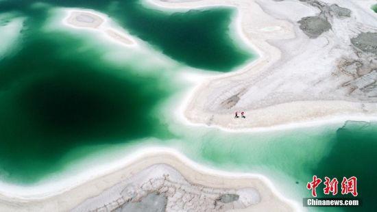 """7月25日,青海省海西蒙古族藏族自治州境内,形态迥异、深浅不一的盐池宛如一块块晶莹剔透的""""翡翠""""。约6平方公里的""""翡翠湖""""名为大柴旦湖,是原大柴旦化工厂盐湖采矿队采矿区,经多年开采形成采坑,变成了如今美丽的""""翡翠湖""""。站在湖边,宛若镜面般的湖面倒影着蓝天白云和皑皑雪峰,宛如仙境。图为清澈湛蓝的湖水。 刘忠俊 摄"""