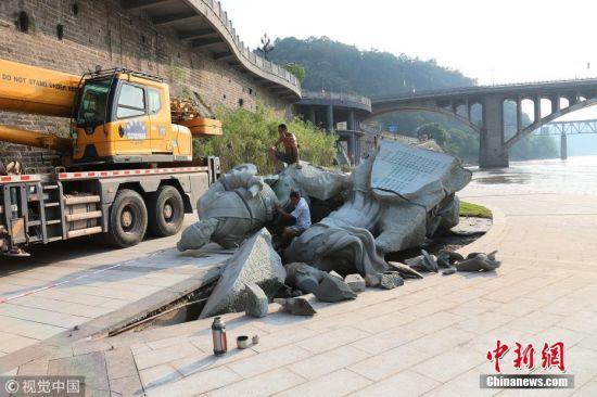 """8月5日一早,有市民来到岷江边跑步发现,这一次,两人均未抵抗住洪峰,苏轼、黄庭坚""""双双醉倒""""。在此前的洪峰冲击中,雕塑之一的苏轼像被洪水冲垮。此次洪峰通过时,雕塑刚刚被修复加固不到10天,没想到再次被冲毁。这次,两尊雕塑连同底座一起倒下,都有不同程度的开裂。其中一个头部已经断开。 图片来源:视觉中国"""
