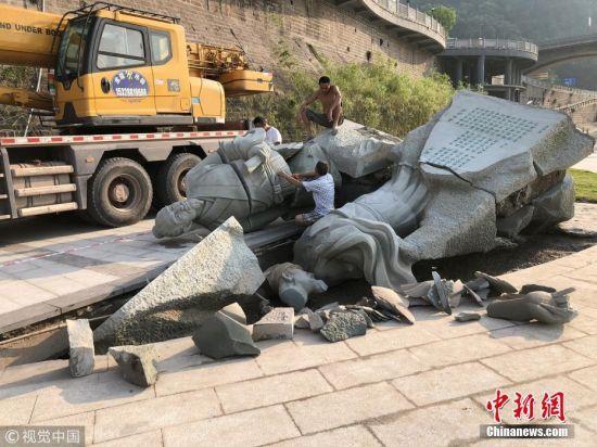 """此次洪峰过后,雕塑被整体冲倒,连基座也被洪水""""连根拔起""""。黄庭坚雕塑裂开,苏东坡雕塑则碎裂在地身首分离,手也断裂被压在坑底。相关负责人表示,他们将考虑把雕塑换个位置,任何雕塑都经不起这种横向洪峰带来的冲击。 图片来源:视觉中国"""