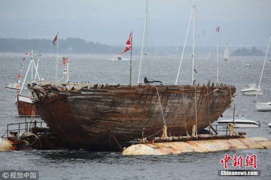 """当地时间2018年8月18日,探险家罗尔德・阿蒙森曾使用的北极探险船""""莫德号""""在被打捞出水后抵达挪威阿斯克尔。这艘沉没了80多年的探险船此后将在这里得以保存。 图片来源:视觉中国"""