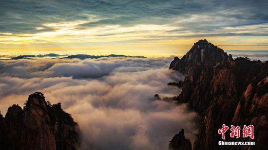 9月13日晨,安徽黄山风景区诸峰为云雾环绕,时隐时现。登高望远,莲花峰、天都峰,以及西海群峰被白白厚厚的云层包裹,形态奇美的黄山松,青褐色的山石与云海交相映衬,把黄山装扮得宛如水墨画卷。图/文 刘浩 叶永清