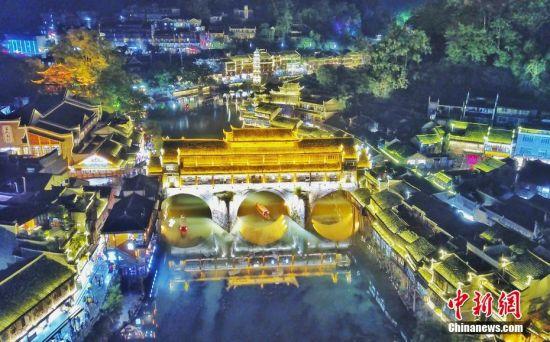 9月18日晚,游人在湖南凤凰古城体验夜游沱江。沱江两岸灯火通明,夜景如画。图为俯瞰凤凰古城夜景。中新社记者 杨华峰 摄
