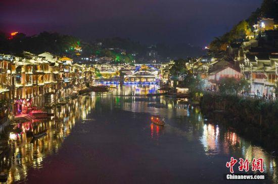 9月18日晚,游人在湖南凤凰古城体验夜游沱江。沱江两岸灯火通明,夜景如画。中新社记者 杨华峰 摄