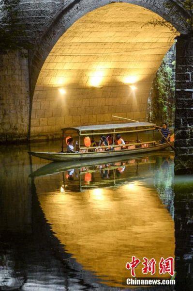 9月18日晚,游人在湖南凤凰古城体验夜游沱江。沱江两岸灯火通明,夜景如画。图为游人乘船经过虹桥桥洞。中新社记者 杨华峰 摄