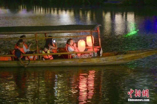 9月18日晚,游人在湖南凤凰古城体验夜游沱江。沱江两岸灯火通明,夜景如画。图为游人在木船上欣赏美景。中新社记者 杨华峰 摄