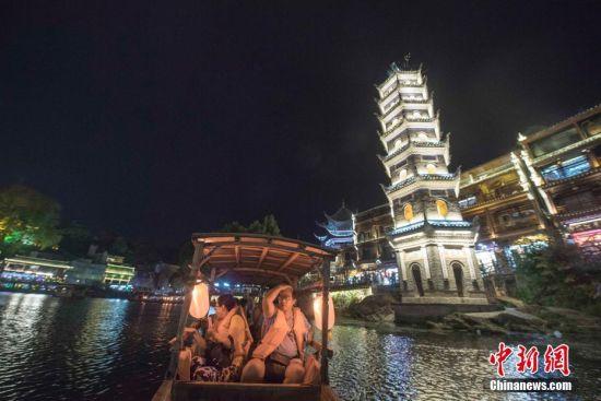 9月18日晚,游人在湖南凤凰古城体验夜游沱江。沱江两岸灯火通明,夜景如画。图为游人乘船体验沱江夜游。中新社记者 杨华峰 摄