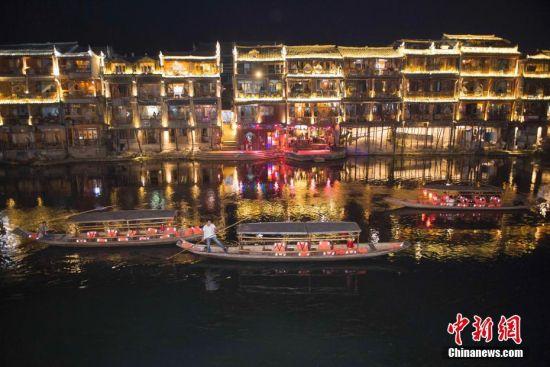 9月18日晚,游人在湖南凤凰古城体验夜游沱江。沱江两岸灯火通明,夜景如画。图为船工划着游船在沱江上行驶。中新社记者 杨华峰 摄