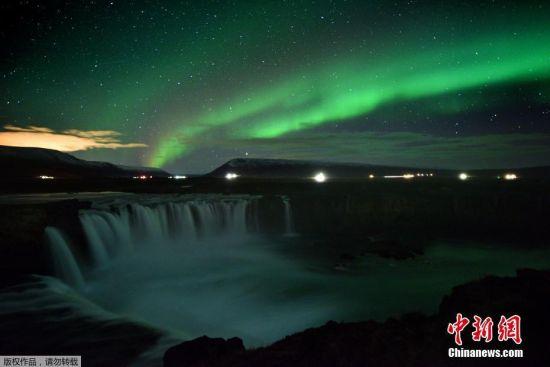 当地时间2018年10月14日,冰岛Thingeyjarsveit,当地一瀑布上空出现极光,光影绚烂似童话世界。