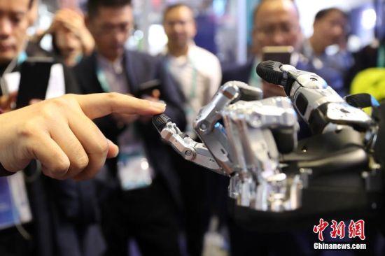 """11月7日,进博会上明星展品最""""巧""""五指仿生机械手吸引众人与其亲密接触。中新社记者 张亨伟 摄"""