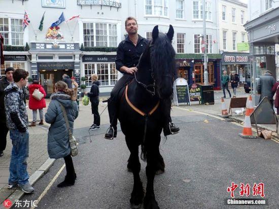 当地时间2018年11月6日,乔纳森-马歇尔(Jonathan Marshall)骑着他那匹引人注目的黑色骏马阿玛迪斯(Amadeus),去了巴恩斯特珀尔的商业街。50岁的乔纳森来自英国康沃尔郡的Gooseham(位于布德以北6英里处),他把黑马阿玛迪斯拴在劳埃德银行外(这家银行的商标正好是一匹黑马),接着,乔纳森就进去用支票付钱了,留下逛街的人们在一旁看得目瞪口呆。图片来源:东方IC 版权作品 请勿转载