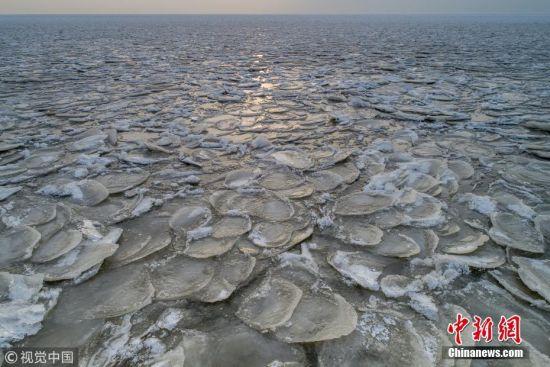 """11月24日下午,摄影师在进入冬季黑龙江东南部中俄界湖兴凯湖看到,浩瀚千里的湖面不再波涛汹涌,小兴凯湖蔚蓝犹如平镜,大兴凯湖银白无限。走到冰封的湖面近处观看,封冻的大湖湖面犹如浪花被凝固,千姿百态。据岸边渔民介绍,今年大湖属于""""武封"""",是由于气温突然下降造成的,这也是少有的现象,和往年的""""文封""""形成的大冰块区别很大。孙长山 摄 图片来源:视觉中国"""