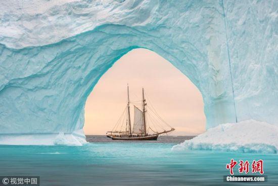 """近日,一名摄影师在格陵兰岛捕捉到了一副风景如画的景象,一艘双桅帆船精完美地嵌入了格陵兰岛沿岸一座巨大的水蓝色冰山中间的拱门之中,看起来既精致又美妙。据悉,这名摄影师名叫詹姆斯拉什沃思(James Rushworth),来自英国。当天,32岁的詹姆斯为了这张合影,冒着低至零下10摄氏度的气温在格陵兰岛的海上耐心地等待着,当双桅帆船正好位于冰山拱门中间,他按下了快门。照片中,长108英尺(约33米)的双桅帆船在300英尺(约91.5米)高的冰山衬托之下,显得十分袖珍,令人不禁感叹。对此,詹姆斯表示:""""我们出海航行时恰巧看到了这些大冰山。拍照时我在那艘双桅帆船的姊妹船上,跟着帆船刚好可以确定拍摄角度。我们十分小心,不能离得太近,怕冰山会突然倒塌,掀起巨大海浪。拍照前我注意力特别集中,拍完了我就坐在那儿欣赏冰山美景了,真的实在是太美了。""""图片来源:视觉中国"""