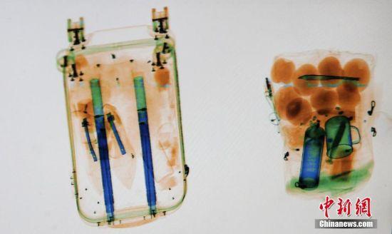 1月22日,2019年春运第二天,在江苏扬州汽车站的安检处,所有进站旅客的行囊都要进行安检,接受X光检查,旅客的行囊通过X光安检机,不同物品不同材质在监视器上呈现出五颜六色的水彩画。图为在安检仪X光扫描下的春运行囊。孟德龙 摄