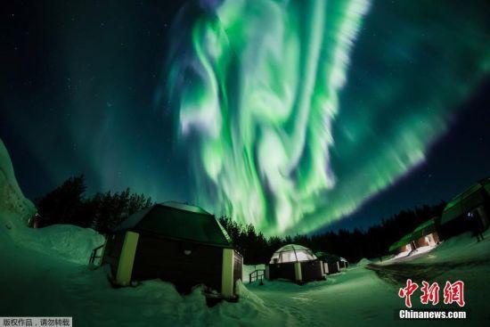 """近日,来自澳大利亚科廷科技大学的Jingyi Zhang和母亲前往冰岛旅行,幸运地见到了北极光,当她母亲走到雪地中间抬头仰望之时,北极光恰好变幻成""""巨龙""""的形状,这精彩的一幕被Jingyi捕捉下来。"""
