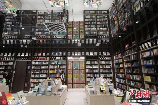 """3月5日,郑州一家高颜值书店钟书阁成为市民拍照打卡的新晋""""网红地"""",书店内各处天花板上全都缀满了镜子,使得书店空间显得无比高挑。店内的陈设反射在天花板上,形成了独特的视觉效果。原本就有三米多高的书架反射在镜面上,仿佛""""长高""""了一倍,显得密集且壮观,有如""""空中楼阁"""",看上去十分酷炫;而儿童阅读区反射在镜面上时,五颜六色的小书架仿佛变成了一座迷宫,似乎在无限向远处延伸。图片来源:东方IC 版权作品 请勿转载"""