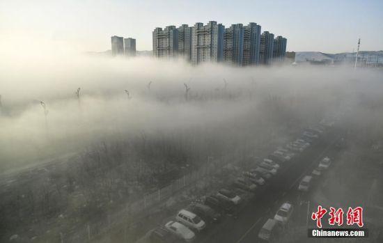 """连日来,随着气温升高,积雪快速融化,新疆乌鲁木齐市城北区域持续大雾天气,夜晚能见度低于百米的雾气会一直持续到天亮。3月17日清晨,该市城北区域持续一夜的浓雾在晨光中渐渐散去,""""藏身""""于迷雾之中的高层楼宇,朦朦胧胧、若隐若现,远观仿若""""海市蜃楼"""",整个画面如仙境般的幽美。刘新 摄"""