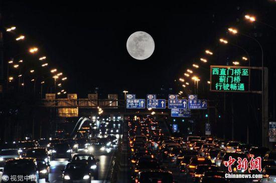 """2019年3月21日,北京,当日正值春分节气,月亮从正东方升起,京城呈现长安街""""悬日""""景观,恰好又遇农历十五圆月,亦是今年最后一次""""超级月亮"""",造就了难得一见的奇观。(二次曝光) 图片来源:视觉中国"""