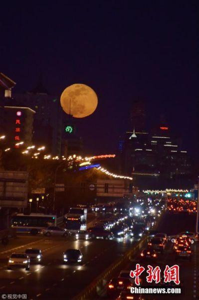 """2019年3月21日,北京,当日正值春分节气,月亮从正东方升起,京城呈现长安街""""悬日""""景观,恰好又遇农历十五圆月,亦是今年最后一次""""超级月亮"""",造就了难得一见的奇观。北马摄影 图片来源:视觉中国"""
