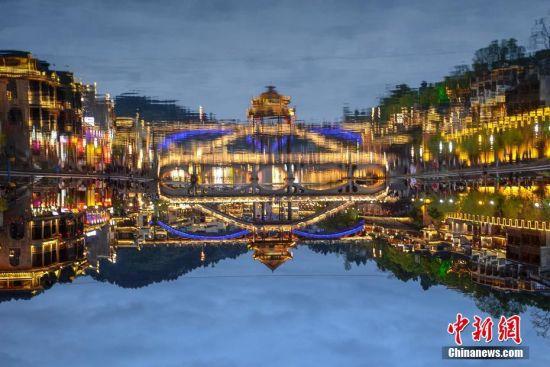 4月11日,湖南凤凰古城夜景吸引了众多游人前来游玩,古色古香的吊脚楼、木桥、城楼等建筑倒映在沱江河中,让人行走在古城仿佛置身于梦境。杨华峰 摄