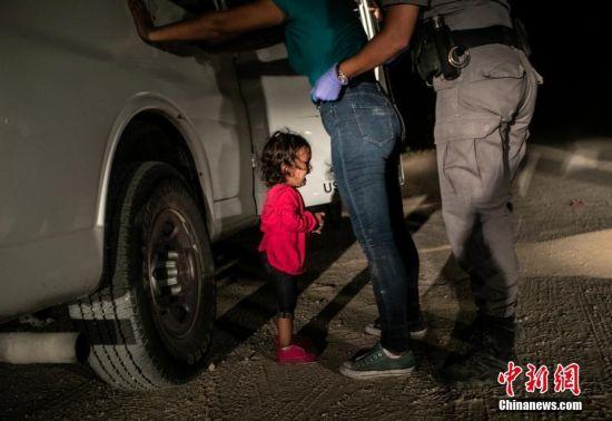 2019荷赛奖年度图片:美墨边境哭泣的小女孩 John Moore(Getty Images) 摄 当地时间2018年6月12日,美国得克萨斯州麦卡伦,美墨边境上,,洪都拉斯移民Sandra Sanchez被边防警拦下搜身,她的女儿Yana站在一旁被吓哭。