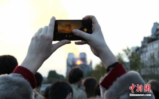 当地时间4月15日晚,法国首都巴黎的著名地标巴黎圣母院发生大火,受损严重。巴黎圣母院大火引发民众高度关注,众多民众在现场附近聚集。中新社记者 李洋 摄
