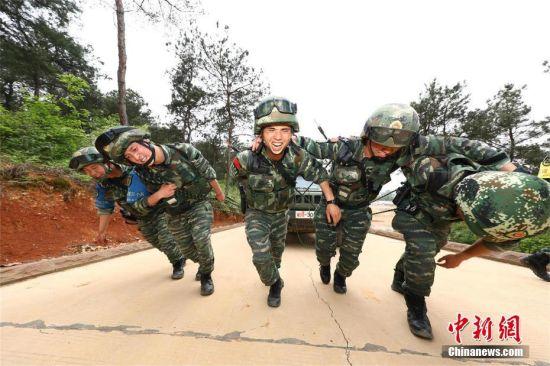 """近日,武警武汉支队开展了为期7天6夜的""""魔鬼周""""极限训练。特战队员在每天训练16个小时以上,人均负重不低于25公斤,徒步行军总里程不少于150公里的情况下,开展了融合战术、技能、体能、心理于一体的30多个课目训练。图为坡地推车训练。高鹏 摄"""