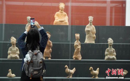 """4月24日,由中国文化和旅游部、国家文物局联合主办的""""归来――意大利返还中国流失文物展""""在中国国家博物馆开幕。图为观众在展出文物前拍照。中新社记者 张兴龙 摄"""
