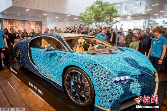 当地时间5月16日,丹麦,世界首辆带有引擎的真正乐高汽车亮相丹麦比隆Lego House。图为观众在观摩乐高汽车。