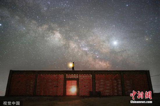 5月24日-26日,甘肃酒泉,摄影爱好者用镜头记录敦煌鸣沙山、玉门关的星空。敦煌作为古代丝绸之路的重要节点之一,其璀璨的星空却鲜有人知。图为5月24日,在甘肃敦煌阳关镇,摄影爱好者在葡萄晾房上遥望星空。王俊峰 摄 图片来源:视觉中国