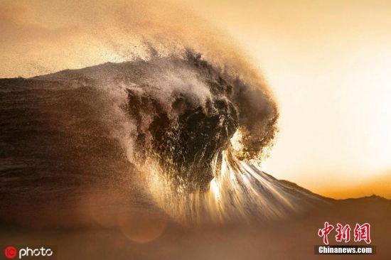 2016年6月12日报道(具体拍摄时间不详),滔天巨浪瞬息万变,却总能在摄影师的镜头下翻涌变幻出各种奇幻美景,摄影师Ben Thouard就在属波利尼西亚塔希提岛拍摄了日落时分的翻天巨浪,滚滚而来的浪花在夕阳的映衬下泛着闪闪金光,美幻场景令人迷醉。图片来源:ICphoto