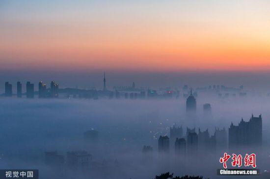 6月10日,日落时分,浮山上俯瞰青岛,城区出现平流雾景观。路鹏宇 摄 图片来源:视觉中国