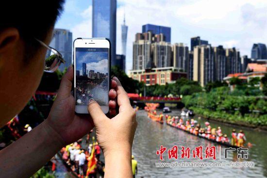 岸上的人们纷纷用手机拍下龙舟划过的盛景。