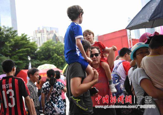 外国游客挤在人群中观看端午节龙船招景。