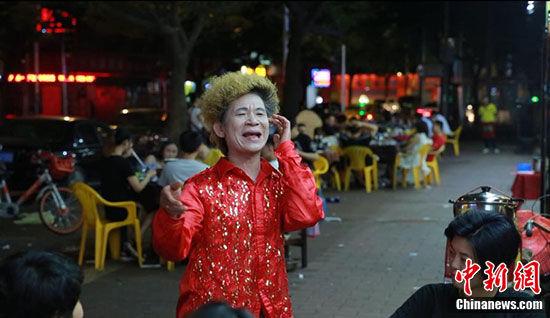 炒螺明男扮女装在宵夜档模仿梅艳芳唱歌 韦杰夫 摄