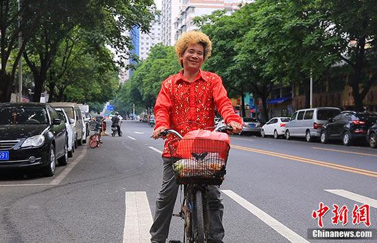 清晨,宵夜档收市,炒螺明骑单车回家。 韦杰夫 摄