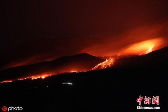 """当地时间7月27日,意大利西西里岛,埃特纳火山持续喷发,山体出现新裂缝岩浆滚滚流动如赤色""""火河""""。意大利西西里岛埃特纳火山19日夜间开始喷发,致使岛上两座机场一度关闭。图片来源:ICphoto"""