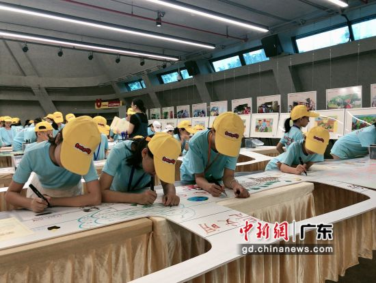 小朋友们在小火车车厢上进行彩绘创作。(摄影:郑小红)