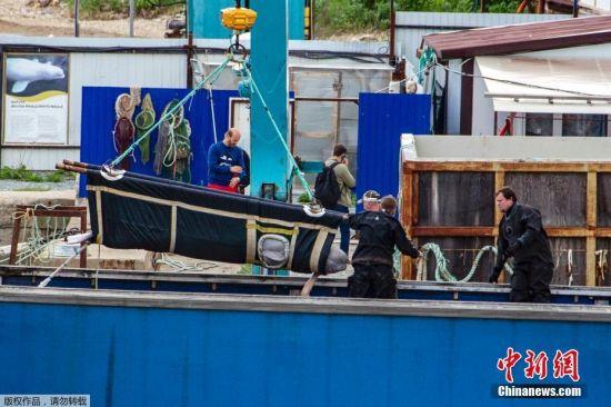 """6月27日,首批鲸鱼被释放到鄂霍次克海,包括两只虎鲸和六只白鲸。7月16日释放了第二批,包括3只虎鲸。第三阶段放归行动于8月1日开始。俄罗斯自然资源与生态部部长德米特里・科贝尔金此前表示,""""鲸鱼监狱""""中的其余5只虎鲸将在夏末之前被放归自然。图为当地时间6月20日,俄罗斯,海参崴,工人们在斯雷德尼亚湾用起重机把鲸鱼移走。"""