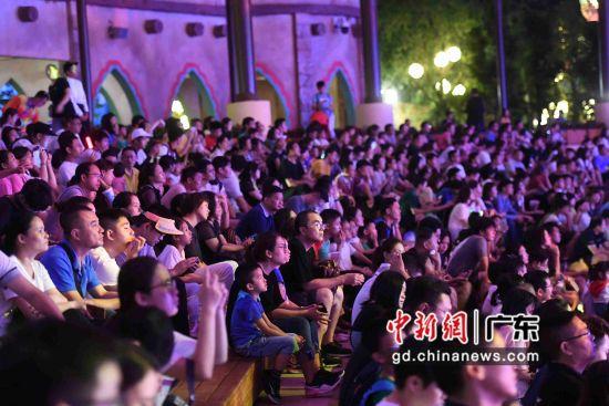 观众在台下欣赏美轮美奂的水幕灯光和精彩的舞蹈表演。
