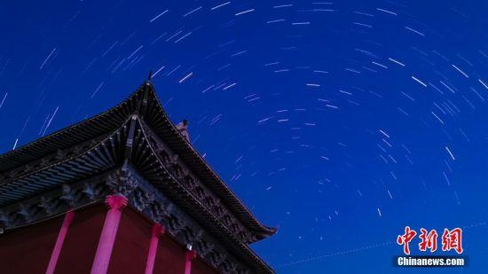 """8月14日凌晨,江西省新余市仰天岗国家森林公园内多重曝光下的星轨图和英仙座流星。8月13日晚至14日凌晨,北半球三大流星雨之一、素有""""圣洛朗的眼泪""""之称的英仙座流星雨如约浪漫来袭。在北半球,英仙座流星雨成为每年暑期的""""定期演出"""",备受期待。英仙座流星雨不但数量多,而且几乎从来没有在夏季星空中缺席过,是目前最活跃、最常被观测到的流星雨之一。赵春亮 摄"""
