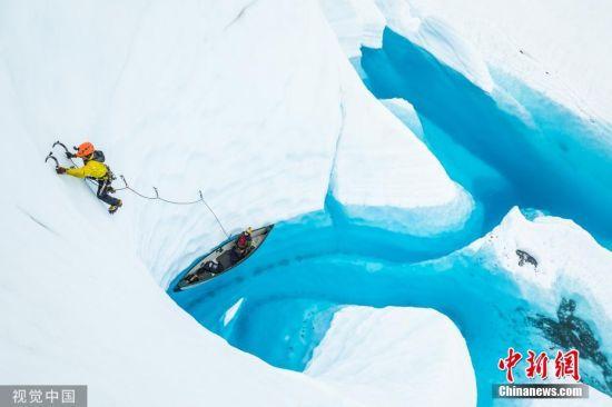 """8月21日消息,27岁的""""冰川导游""""布雷特・温特伯顿、26岁的沃伦・马多克斯和24岁的香农・凯林划着独木舟沿美国阿拉斯加马塔努斯加冰川的冰川隧道前行,并勇敢地翻越50英尺(约合15.24米)高的冰墙,探索冰川另一端美丽的蓝色湖泊。图片来源:视觉中国"""
