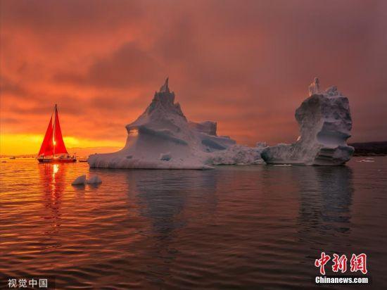9月5日讯(具体拍摄时间不详),格陵兰岛迪斯科湾,一艘挂着红帆的游艇在形状各异的冰山之间航行,为宁静的北极夜晚增添了一抹亮色。图片来源:视觉中国