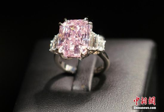 """9月10日,香港苏富比宣布,一枚10.64克拉的紫粉红色内部无瑕钻石戒指将领衔10月7日举行的香港苏富比""""瑰丽珠宝及翡翠首饰拍卖""""专场。该戒指拍卖估价为1.5亿至2亿港元。 中新社记者 张炜 摄"""