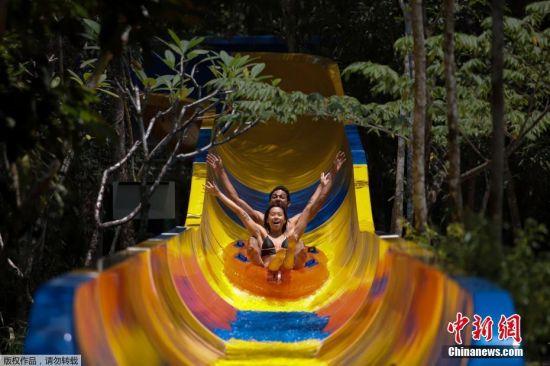 """当地时间9月25日,马来西亚槟榔屿""""逃生主题公园""""的""""世界最长水滑梯""""揭幕,并获得吉尼斯世界纪录。据悉,该水滑梯长达一千余米,游客从滑道在山顶的起点出发,然后蜿蜒穿过茂密的丛林,最后落入游泳池。"""